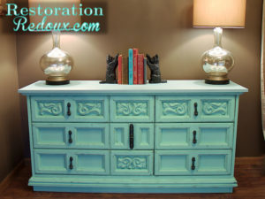 aqua distressed dresser with glass lamps and cat bookends