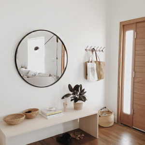 Entry way with round mirror, bench, baskets and coat rack